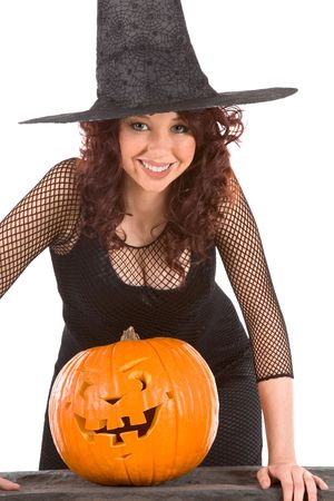 Portrait of busty Latina teenager girl in black Halloween hat and fishnet dress with carved pumpkin (Jack O Lantern) photo