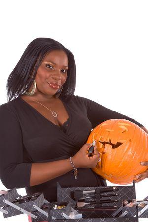 Afro-American make up artist applying makeup on Halloween carved pumpkin (Jack O Lantern) photo