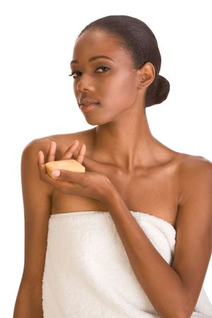 grooming product: Beautiful young African-American woman with Slicked Back Hair wrapped in white bath towel an holding bar of soap preparing for sauna