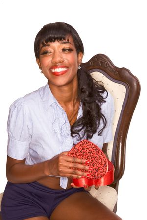 Smiling African-American young woman sitting on chair and holding heart shaped gift box apparently excited by the present photo