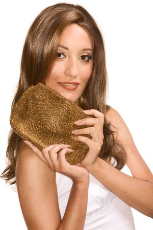 Portrait of young attractive Middle Eastern female in white dress in light brown shiny wig holding golden colored purse photo