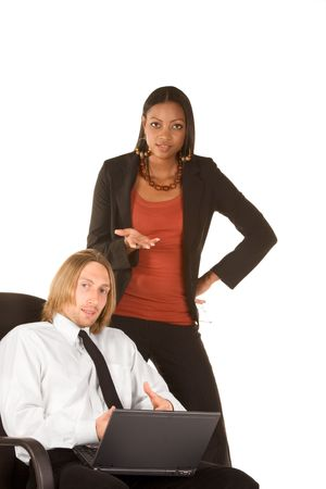 apparently: Caucasian young businessman in white shirt sitting on office chair holding portable notebook computer on his lap and ethnic businesswoman standing by side of him and gesturing apparently asking viewer about something or offering help � Why do you wait? We