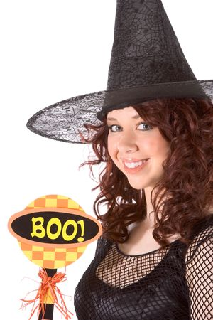 Portrait of Latina teenager girl in black Halloween hat and fishnet dress holding boo! sign photo