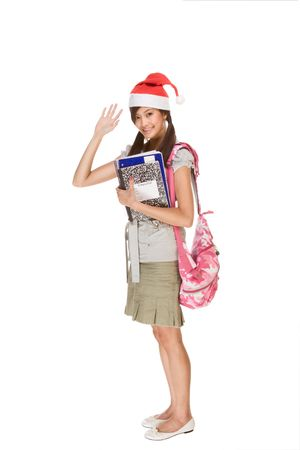 Asian school girl wearing red Santa Claus hat with backpack holding Composition book, notebooks and pen waives her hand making greeting gesture Imagens