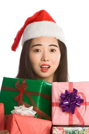 Excited Asian girl Santa Claus hat with pile of Christmas gifts wrapped in colorful paper and decorated by bows photo