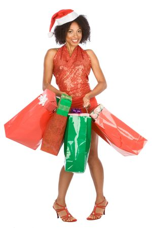 Dark skinned female in sexy outfit holding large amount of shopping bags with Christmas gifts, tired and excited by holiday shopping