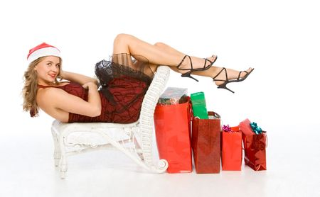 Blonde woman in Santa hat lying down with her legs and high heel shoes over row of colorful red shopping bags filled with boxes of wrapped Christmas presents photo