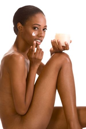 Beautiful nude young African American woman with Slicked Back Hair applying moisturizer on her face