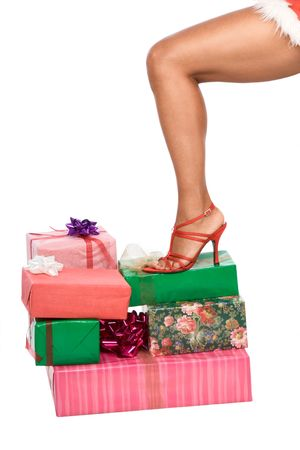 Female Leg in red shoe standing on stack of wrapped gifts photo