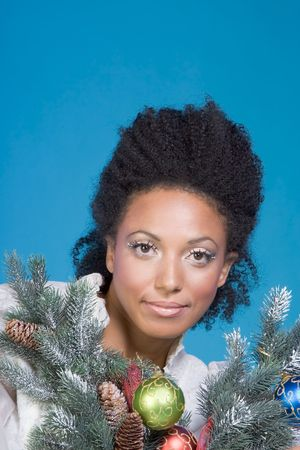 Portrait of mid-aged beautiful Spanish female surrounded by branches of decorated Christmas tree photo