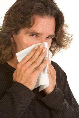 Middle-aged male covers his nose part of the face by paper towel or tissue apparently blowing his
