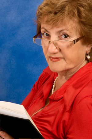 Portrait of senior woman wearing eyeglasses and holding open book in her hands photo