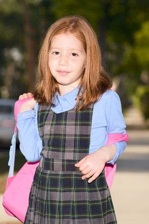 6 years girl: Friendly redhead student young girl wearing school uniform and holding pink backpack  Stock Photo