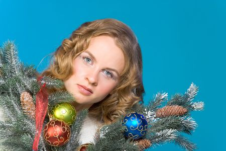 Portrait of young beautiful blonde female surrounded by branches of decorated Christmas tree photo
