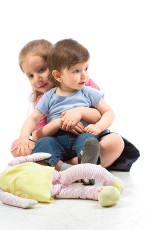 2 5 months: Young girl sitting on floor with her baby brother on her laps and stuffed cloth doll toy is lying in front of them