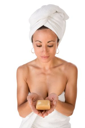 slicked back hair: Portrait of ethnic female wrapped in white bath towel around her body and head and holding bar of soap in her palm Stock Photo