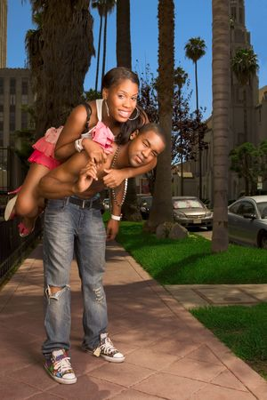 bald girl: Black youthful heterosexual couple making fun on street, female riding on man�s back