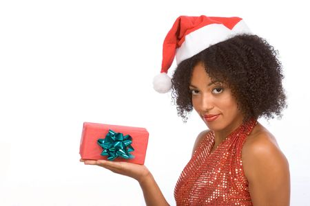 Dark skinned middle aged woman in sexy Mrs. Santa Claus outfit holding on palm of her hand small gift box wrapped in red paper and decorated by green bow photo