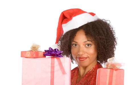 Dark skinned middle aged woman in sexy Mrs. Santa Claus outfit holding stack of gift boxes wrapped in paper and decorated by bows photo