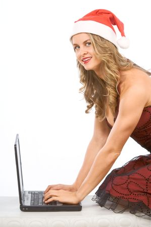 Young beautiful blonde woman in Christmas hat standing on knees with her hands on keyboard of portable notebook computer photo