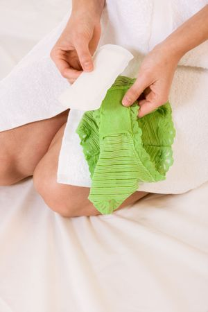 Close up of female hands holding feminine hygienic pad, preparing to stick it to her green panties Stock Photo - 3869692