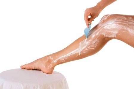 Body hygiene: Woman depilates - scrubs hair removal cream off her leg photo