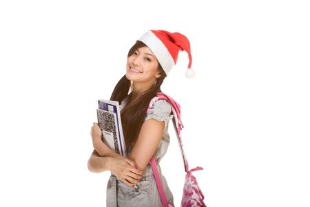 Asian schoolgirl wearing red Santa Claus hat with backpack holding Composition book, notebooks and pen photo