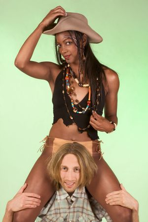 Heterosexual couple of ethnic dark skinned woman and Caucasian man wearing period costumes of risqué provocative Pocahontas and cowboy are playing. Girl is riding on shoulders of the guy photo