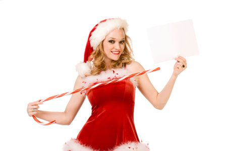Blond sensual pinup woman in Christmas Mrs Santa Claus outfit holding sheet of white paper and points to it by huge candy cane stick. Can be used as greeting card or your text or additional graphics can be added according to needs. photo