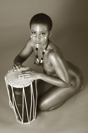 afro american nude: Portrait of African American woman wearing original tribal themed face-paint and necklace playing Conga drum (toned) Stock Photo