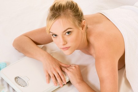 Blond naked woman lying down awaiting spa treatment, surrounded by aromatherapy items and with her hands resting on weight scales  photo
