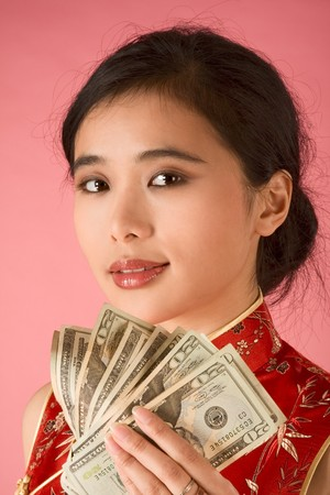 Portrait of young beautiful Chinese female in traditional clothes (cheongsam) holding pile of US paper currency twenty dollars bills. She is proud of her savings or may be she got jackpot photo