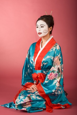 Asian female with geisha style face paint in yukata (kimono) sitting on floor