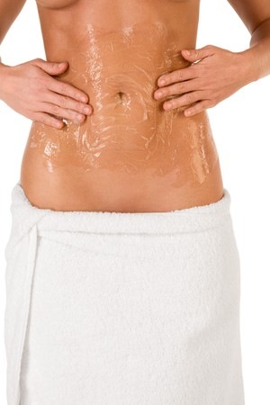 Woman skincare and bodycare procedure - Midsection of well toned female body with hand applying moisturizing gel or scrubbing product on  abdomen belly area. Hips are wrapped in bath towel Stock Photo - 3944429