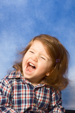 Portrait of emotionally distressed kid with open mouth and long hair (blue background) photo