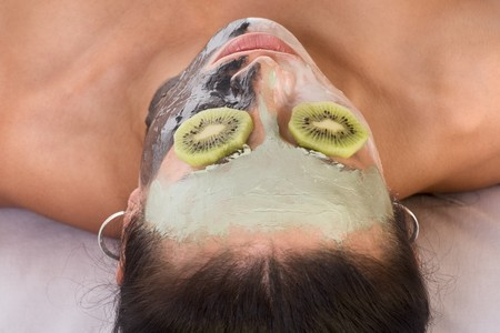 Woman lying down on her back in spa, with special facial mask applied on her face. The mask consist of three colors, each cover different part and eyes are covered by slice of kiwi photo