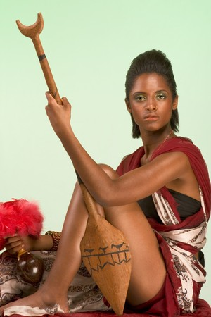 indian artifacts: Dark skinned indigenous female sitting, holding wooden spear and vessel for dry blood with pink feathers Stock Photo