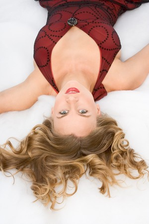 Young sexy blond woman with gorgeous hair in red dress lying on snow like substance photo