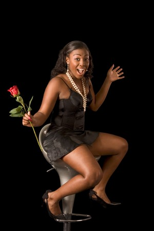 Sensual seductive glamorous black girl in lingerie sitting in chair and holding rose flower. She is apparently excited and show her emotions 免版税图像