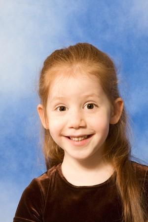 making faces: Red-capelli scuola elementare et� ragazza con i capelli lunghi che si affaccia Archivio Fotografico