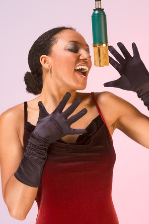 dark skinned sexy female in red concert dress and black gloves sings by microphone