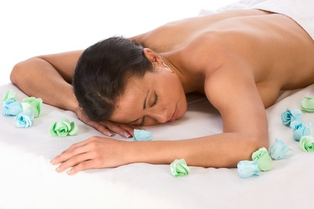 Topless ethnic female lying down and dreaming with closed eyes in spa surrounded by aromatherapy items photo