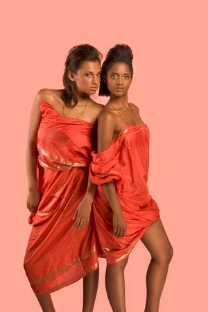 Two dark skinned sensual girls friends wearing Indian red traditional clothing