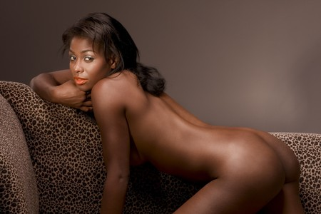 naked black woman: African American hot nude woman on couch in sensual erotic seductive pose, demonstrating her perfectly shaped buttocks Stock Photo
