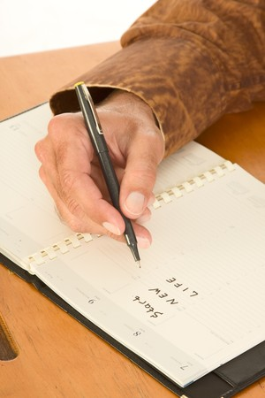 Hand on unidentifiable Caucasian man write in diary using pen planning start new life photo