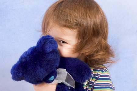peekaboo - shy kid holding blue Teddy bear and peeking from behind blue stuffed animal toy (blue background)