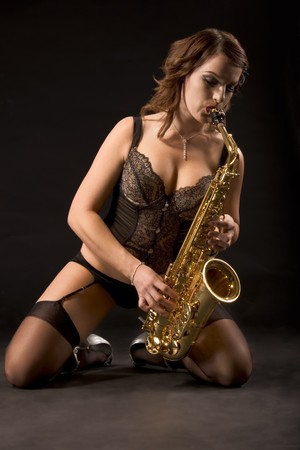 Young woman with saxophone in retro lingerie standing kneeling and playing on her new saxophone