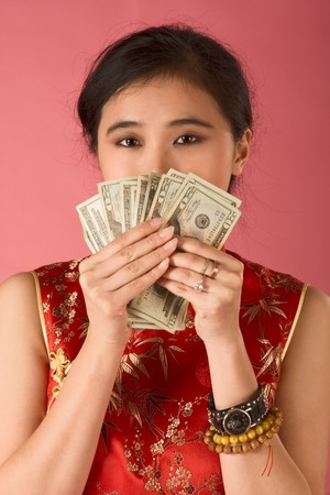 Portrait of young beautiful Chinese female in traditional clothes (cheongsam) holding pile of US paper currency twenty dollars bills, and covering her face by them. She is proud of her savings or may be she got jackpot Stock Photo - 4092237