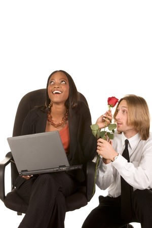 Beautiful ethnic businesswoman in business suit sits on office chair holding portable notebook computer on her lap and Caucasian young man kneeling on her side and giving her red rose flower. Woman half laughs and half shy rolls her eyes up photo