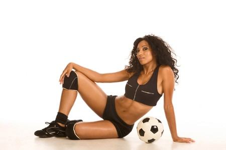 Fitness series sexy mid aged female couch in sport clothes, sitting by black and white football ball photo